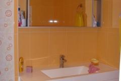Раковина и зеркало на фоне оранжевой плитки